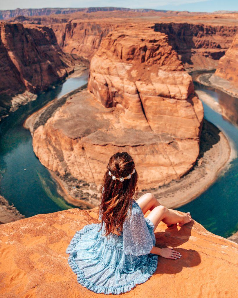 Bettina sitting on the edge overlooking horseshoe bend in Arizona