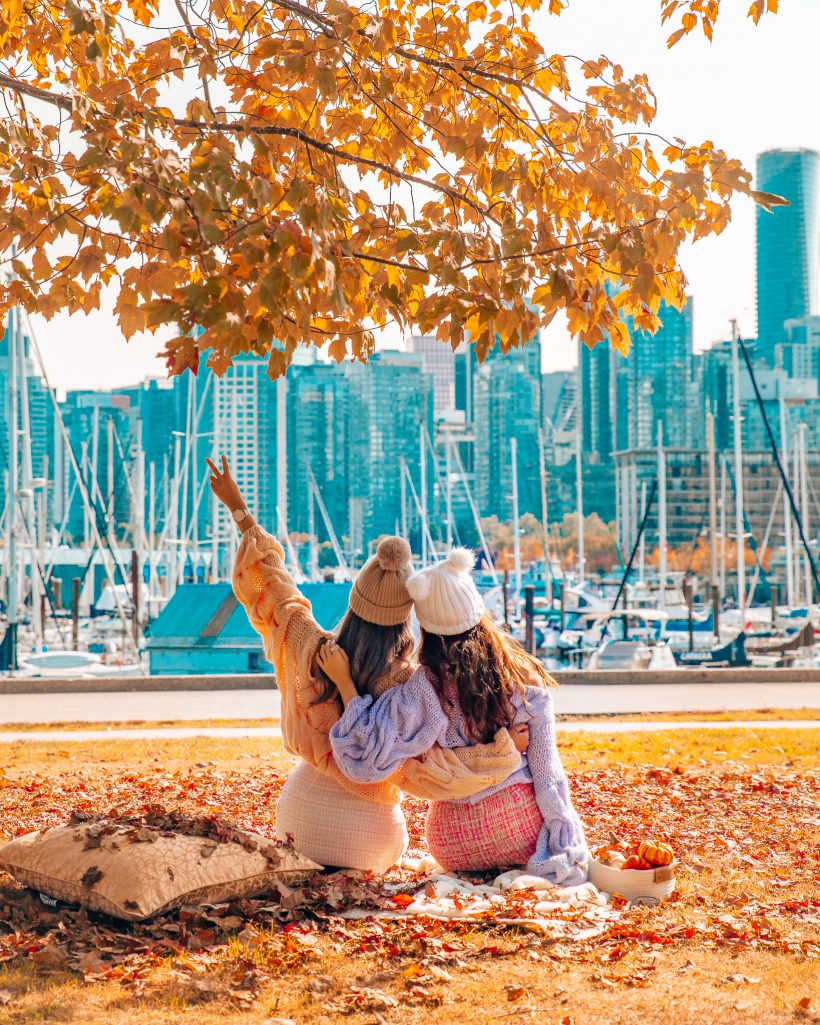 Two Girls sitting in Stanley Park in Vancouver in the Fall