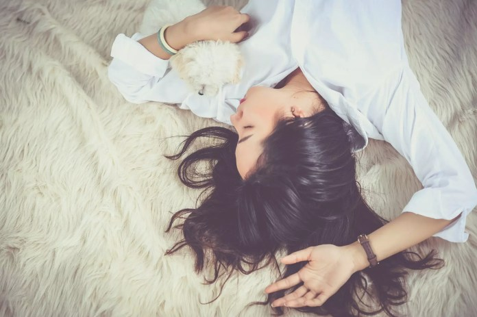 A girl is sleeping while holding her puppy