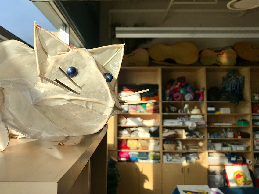 A paper cat sculpture by Holly Sabourin watches over the new fabric studio