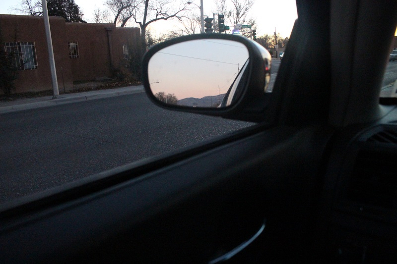 The sunset cast beautiful colors over the Sandia Mountains in Albuquerque, New Mexico, captured in my car's driver side mirror.