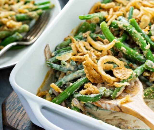 Scooping Out A Big Spoonful Of Green Bean Casserole