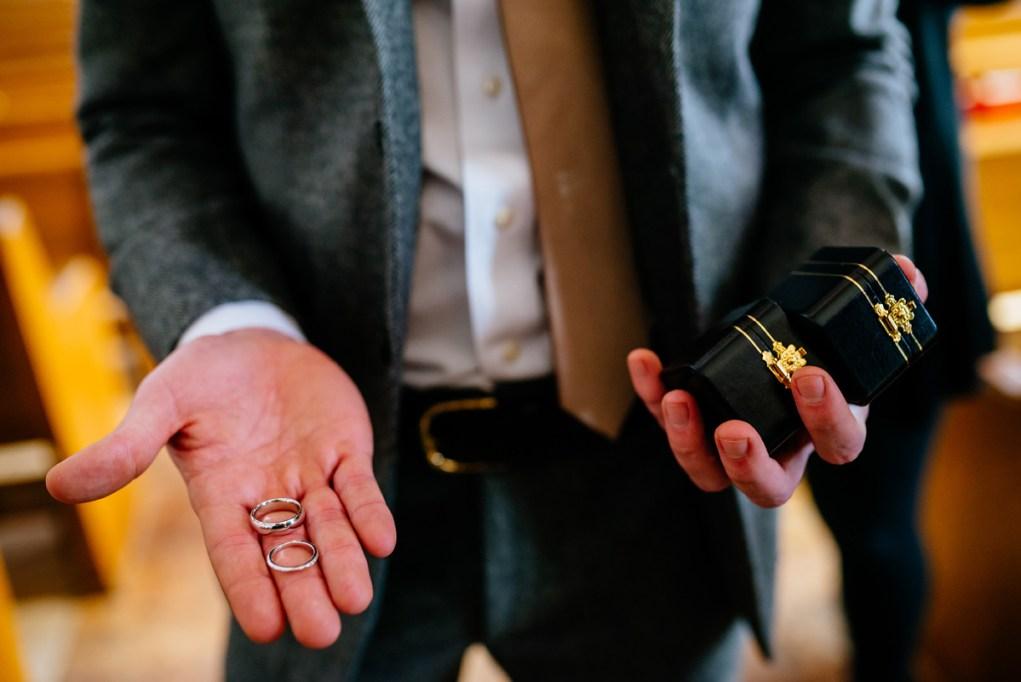 wv winter wedding groomsman holding wedding bands