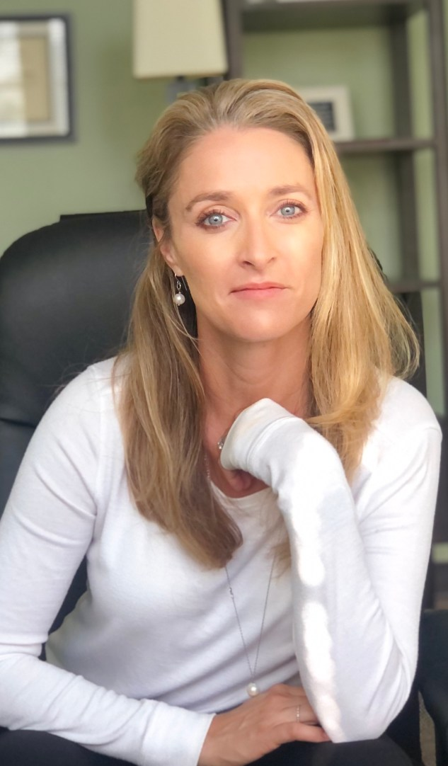 Lauren McMeikan Rosen, LMFT, sitting in her office where she works as an OCD, Anxiety, & Eating Disorder Therapist specializing in CBT, ERP Mindfulness and ACT.