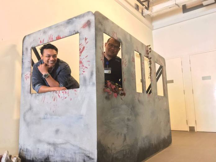Farhan (left) and Shafei (right) in the model train built for Green Room Theatre.
