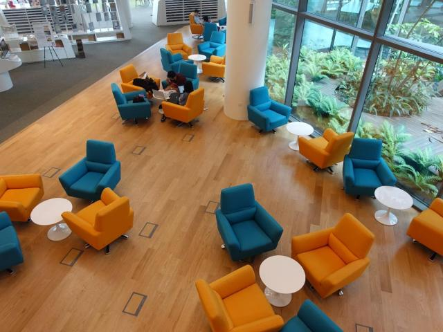 Orange and blue chairs feature prominently in the first floor of the SUTD library.