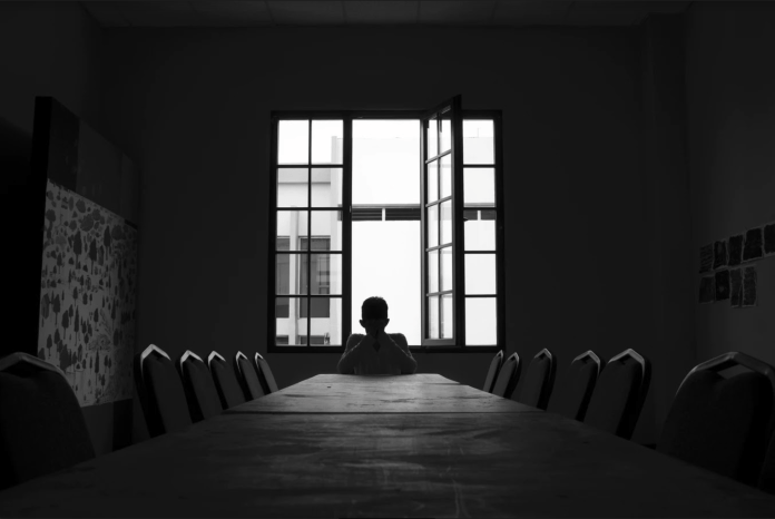 A black and white picture of a frustrated student in empty classroom..