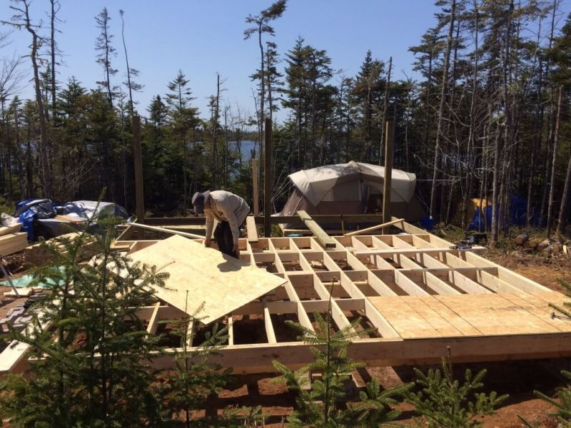 off grid cabin subfloor first sheets being installed