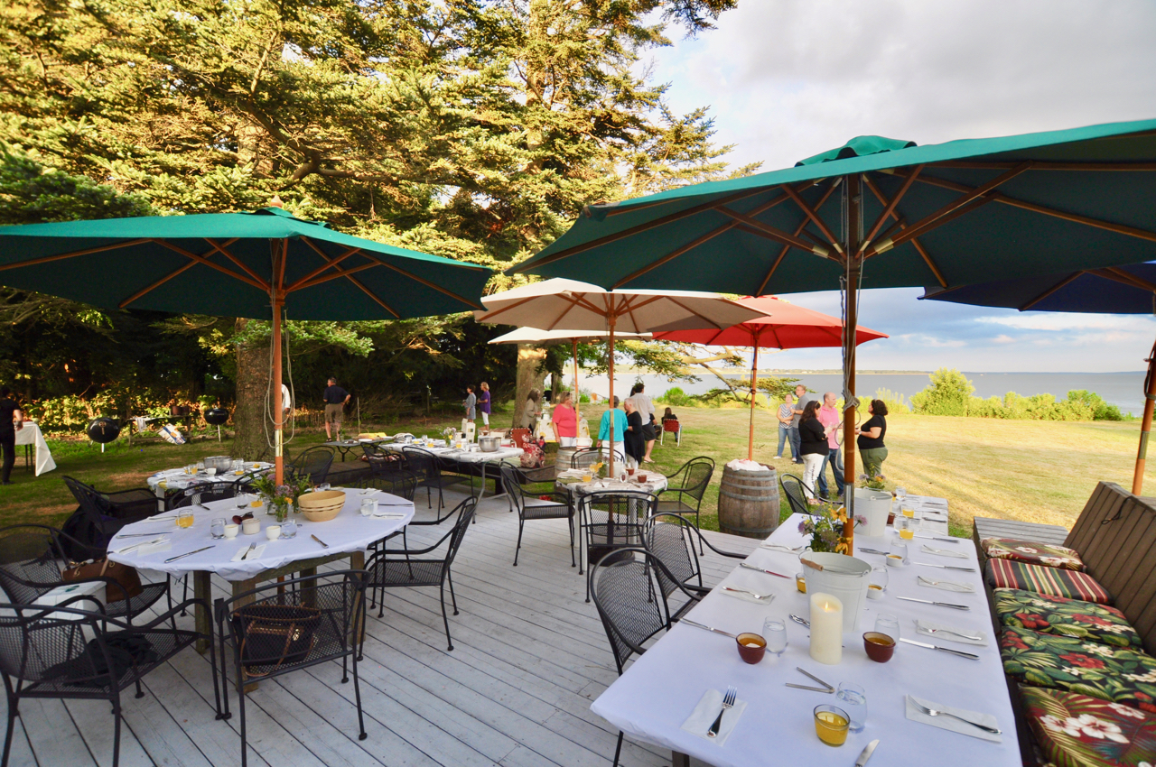 Wine Club event outside on deck with Bay in the background and tables set for dinner.