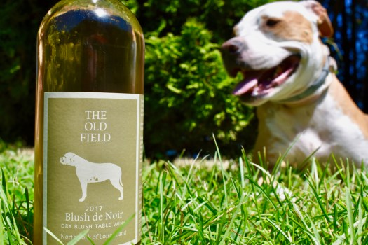 "Our Blush de Noir bottle in the grass with our rescued pitfall dog ""Dilly Dally"" in the background."