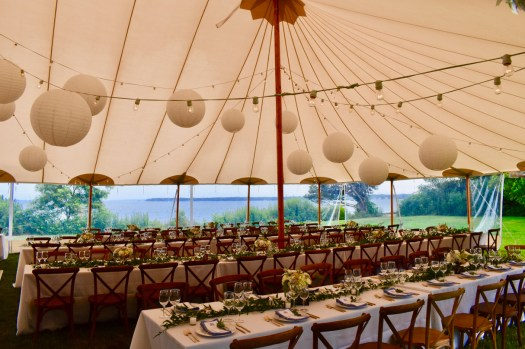 Sperry tent with tables and lights set up.