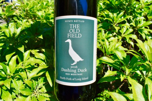 Our Dashing Duck (Field blend red) label in front of green bushes.