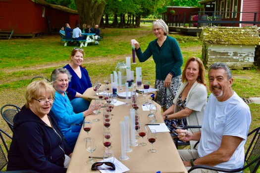 Winemaker Ros doing a tasting of Merlot at a picnic table