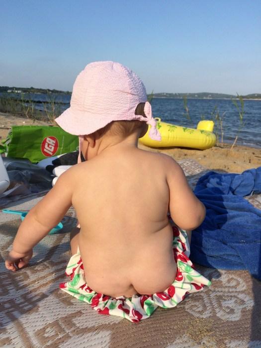 Baby sitting on beach.