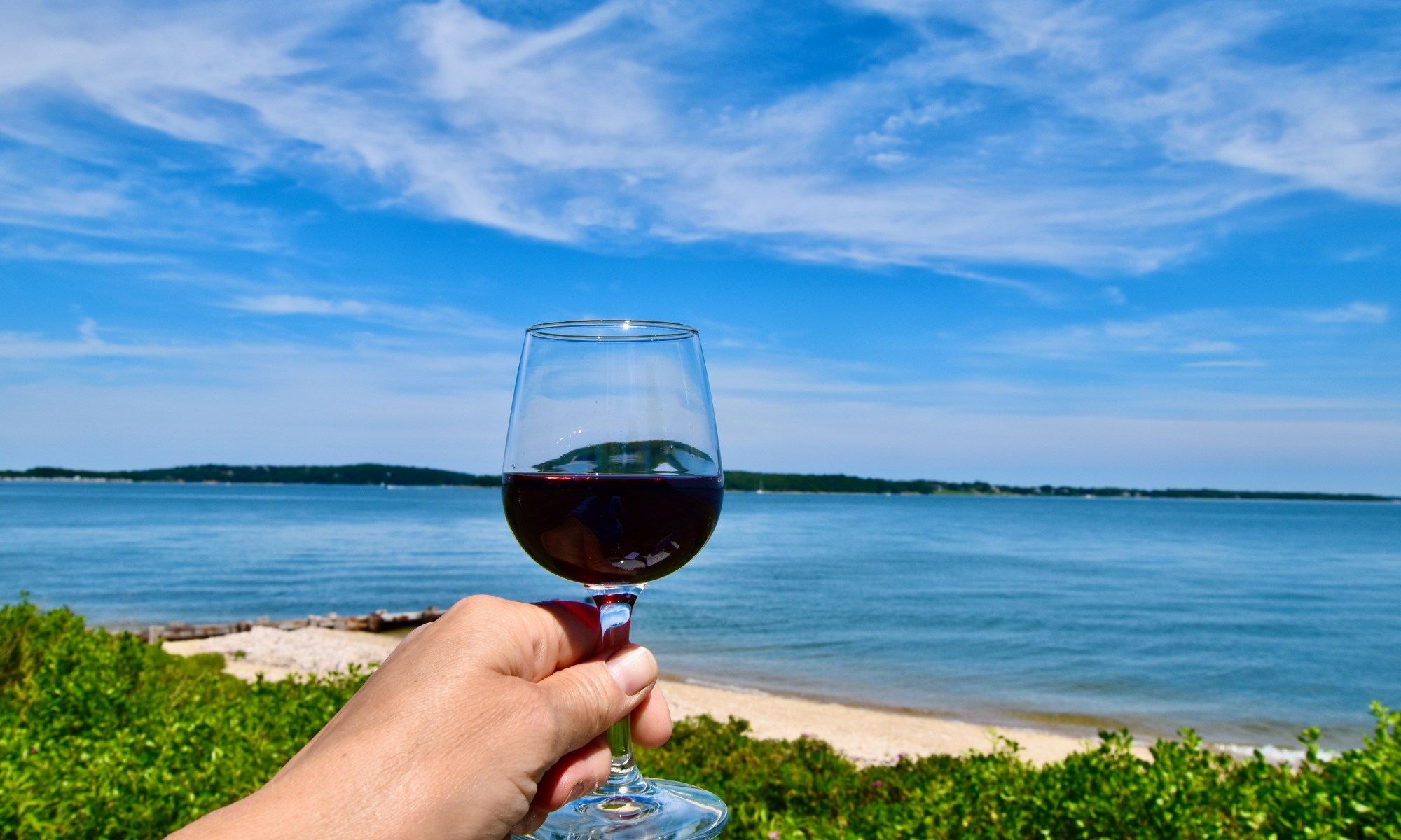 glass of red wine with water in background.