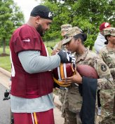 Pfc. Monaisia Young, a unit supply specialist with the 3d U.S. Infantry Regiment (The Old Guard) autographs a Washington Redskins player's helmet during Salute to Service Day, at the Inova Sports Performance Center at Redskins Park on May 24, 2017 in Ashburn, Virginia. During the event, service members were given exclusive access to the training facility and observed the team during a private practice session. (U.S. Army photos by Sgt. Nicholas T. Holmes)
