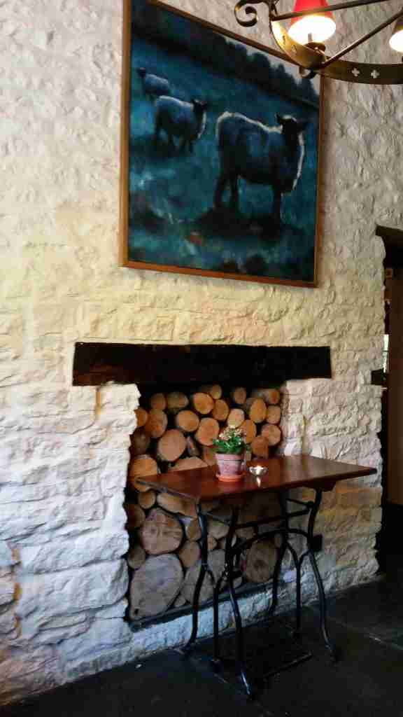 The interior of  The Red Lion showing a  painting of sheep and an old sewing machine table