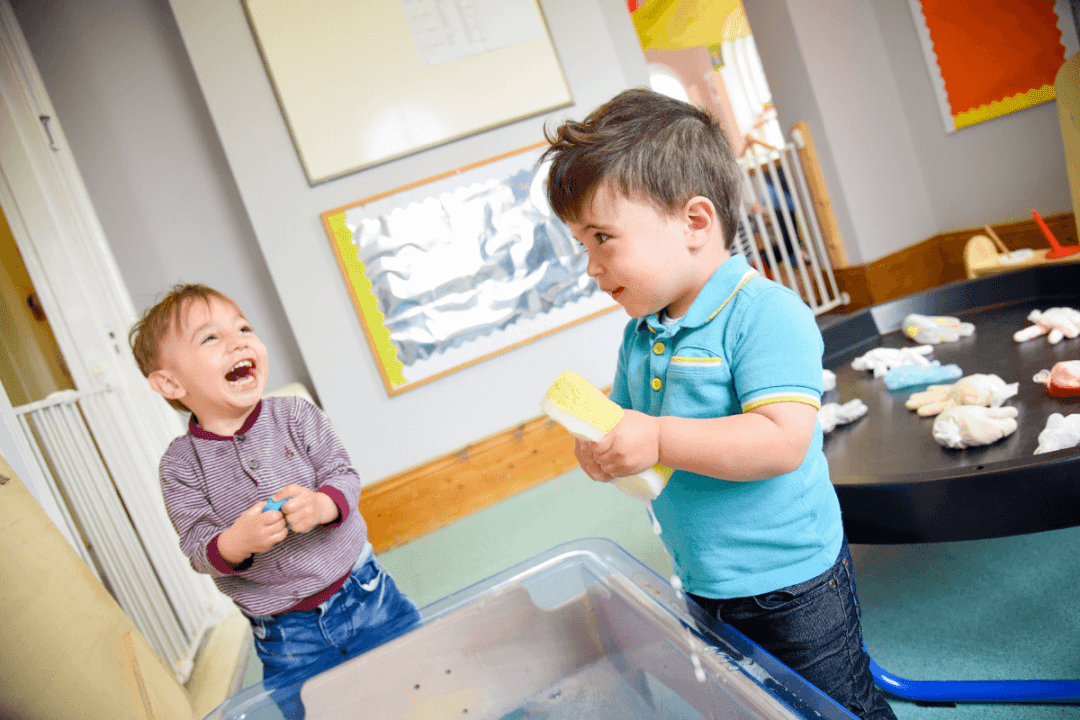 Two toddler boys laughing over the water tray in the Toddler Room at The Old Station Nursery in Dromore