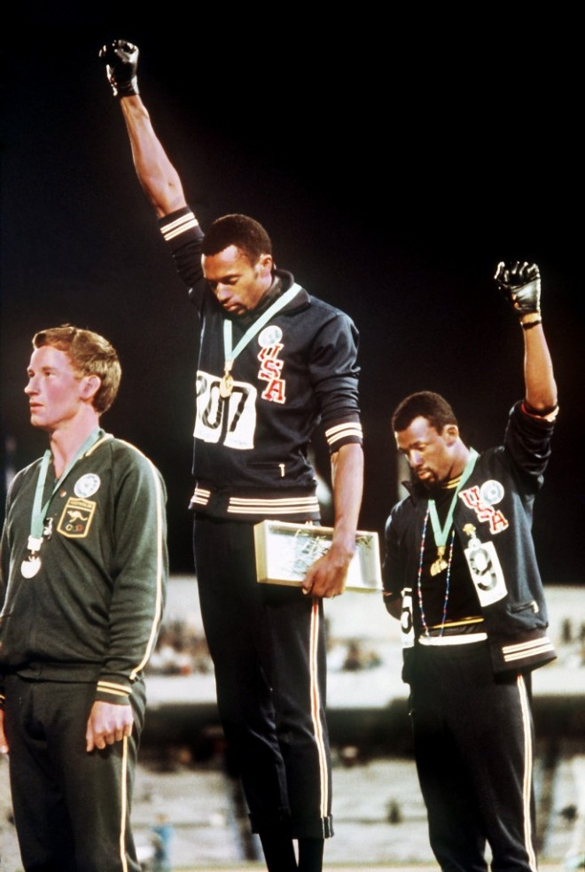 Tommie Smith (center) and John Carlos (right) on the podium after the 200 meter race at the 1960 Summer Games in Mexico City.