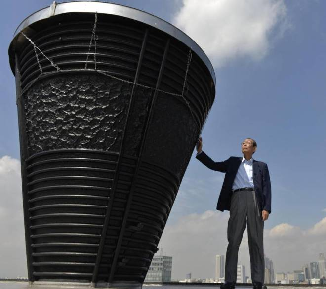 Yoshinori Sakai, who ran the final leg of the torch relay for the 1964 Tokyo Olympics, touches the base of the Olympic torch at National Stadium in Shinjuku Ward in September 2013. | KYODO