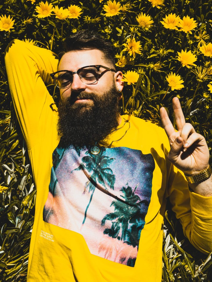 man lying in sunflower with peace sign