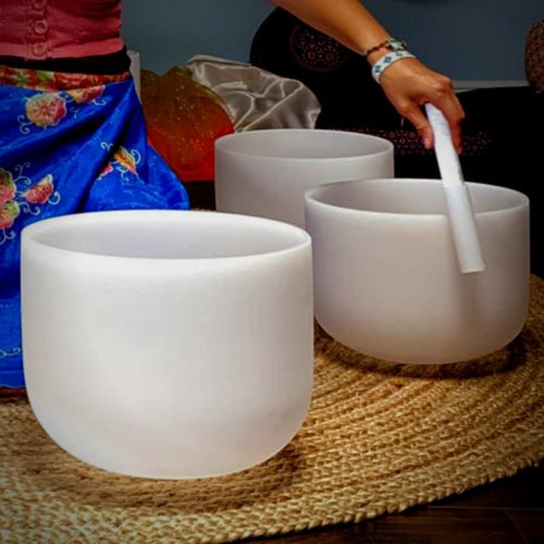 three crystal singing bowls on brown rug being played with silocone striker by woman in blue skirt at the om shoppe