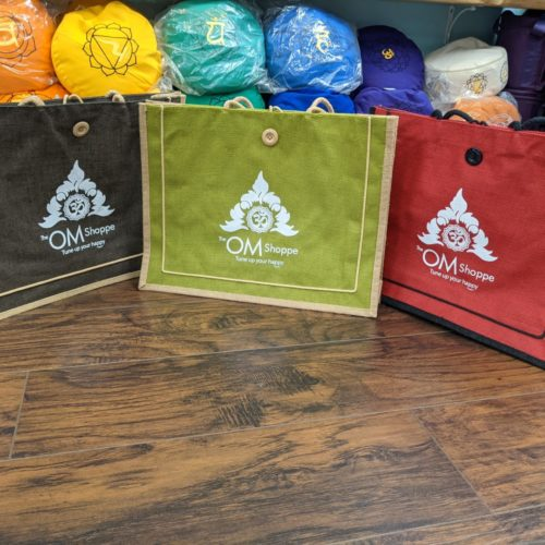 three jute tote bags with the om shoppe logo on them brown, green and red