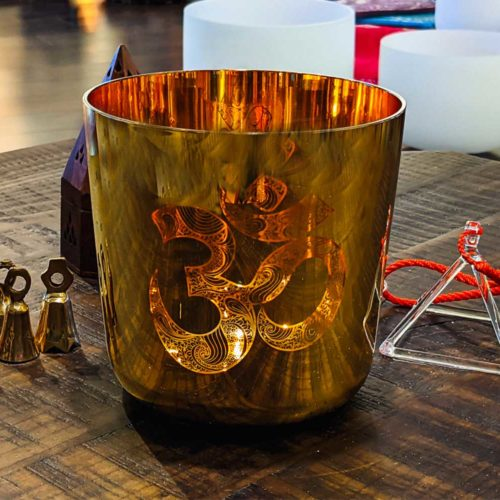 6 Inch Gold Alchemy Hand Inlaid Crystal Singing Bowl on table with bells and a quartz crystal triagnle for sale at the om shoppe