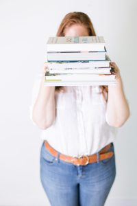 Girl holding stack of textbooks, covering her face