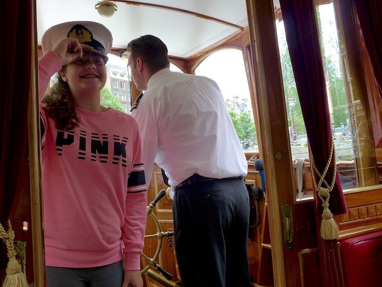 Young girl as captain on canal boat during Eating Amsterdam Dutch food tour.