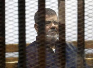 File photo of deposed Egyptian President Mursi listening to his verdict behind bars at a court on the outskirts of Cairo