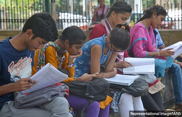 Bengaluru: Students appearing for Common Entrance Test (CET) 2018 busy in last minute revision outside their examination center, in Bengaluru on April 18, 2018. (Photo: IANS)