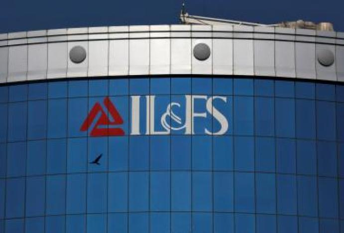 FILE PHOTO: A bird flies next to the logo of IL&FS installed on the facade of a building at its headquarters in Mumbai