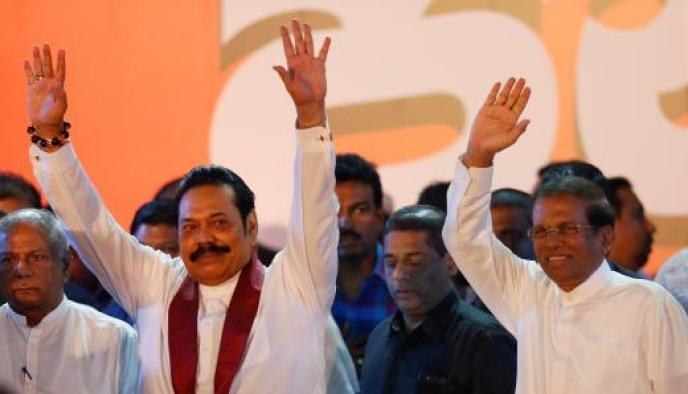 FILE PHOTO: Sri Lanka's newly appointed Prime Minister Rajapaksa and President Sirisena wave at their supporters during a rally near the parliament in Colombo