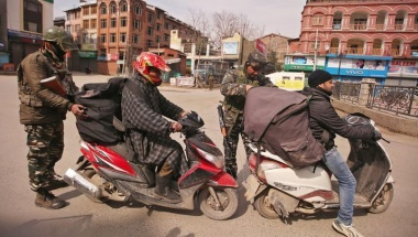 CRPF personnel check the bags of scooterists during restrictions in Srinagar