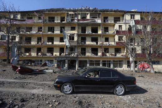 A-man-drives-a-car-past-a-damaged-building-following-recent-shelling-REUTERS