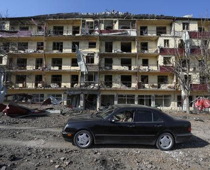 A-man-drives-a-car-past-a-damaged-building-following-recent-shelling-REUTERS