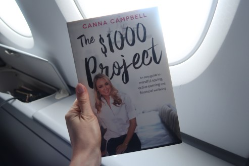 $1000 project book being held up against an aeroplane window