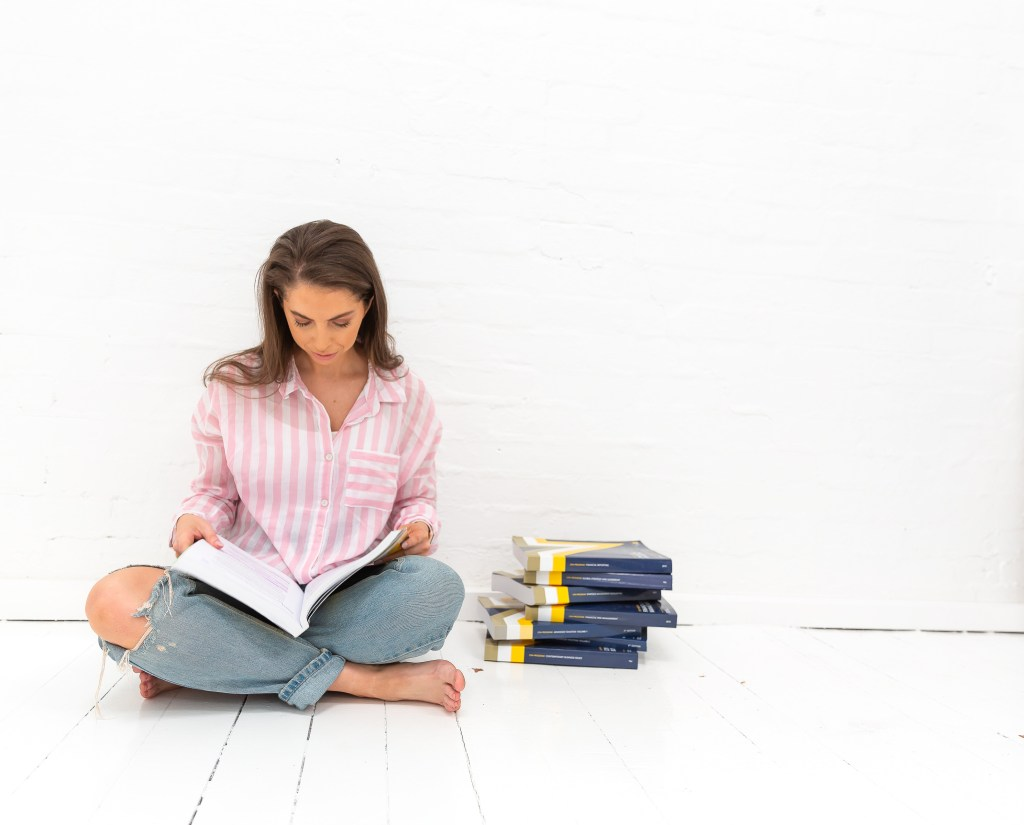 Girl in pink top with jeans on. Sitting on the ground reading CPA books