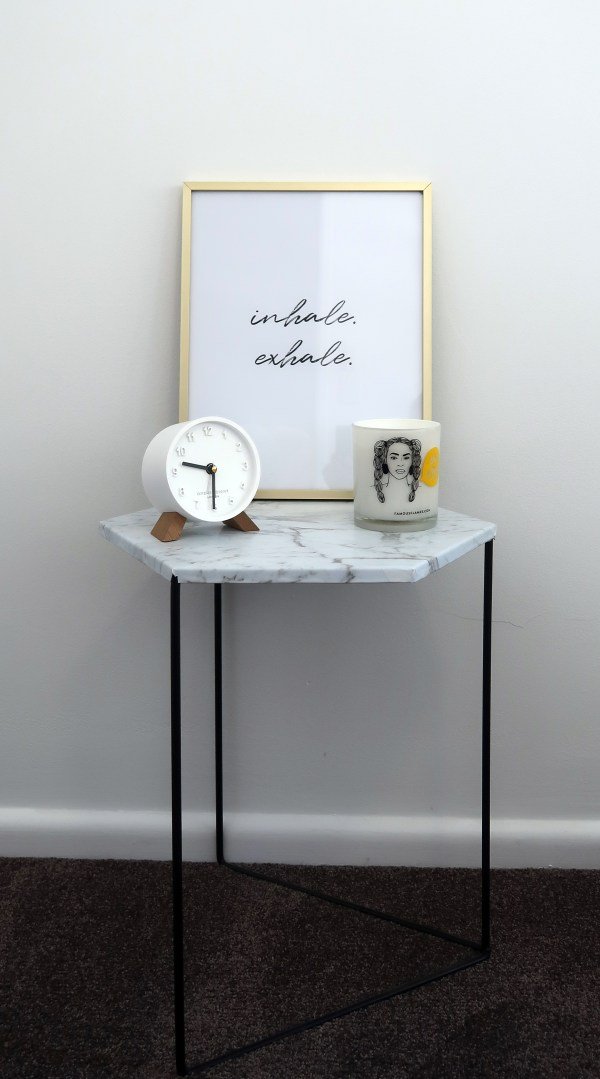 inhale exhale print in a gold frame on a marble table next to a white clock and beyonce candle.