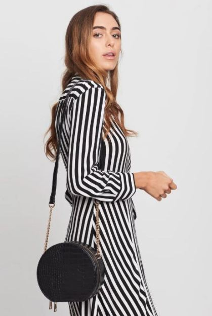 Female in a stripe dress with a back round shoulder bag on