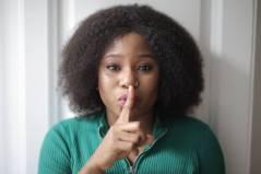 woman doing shh hand gesture