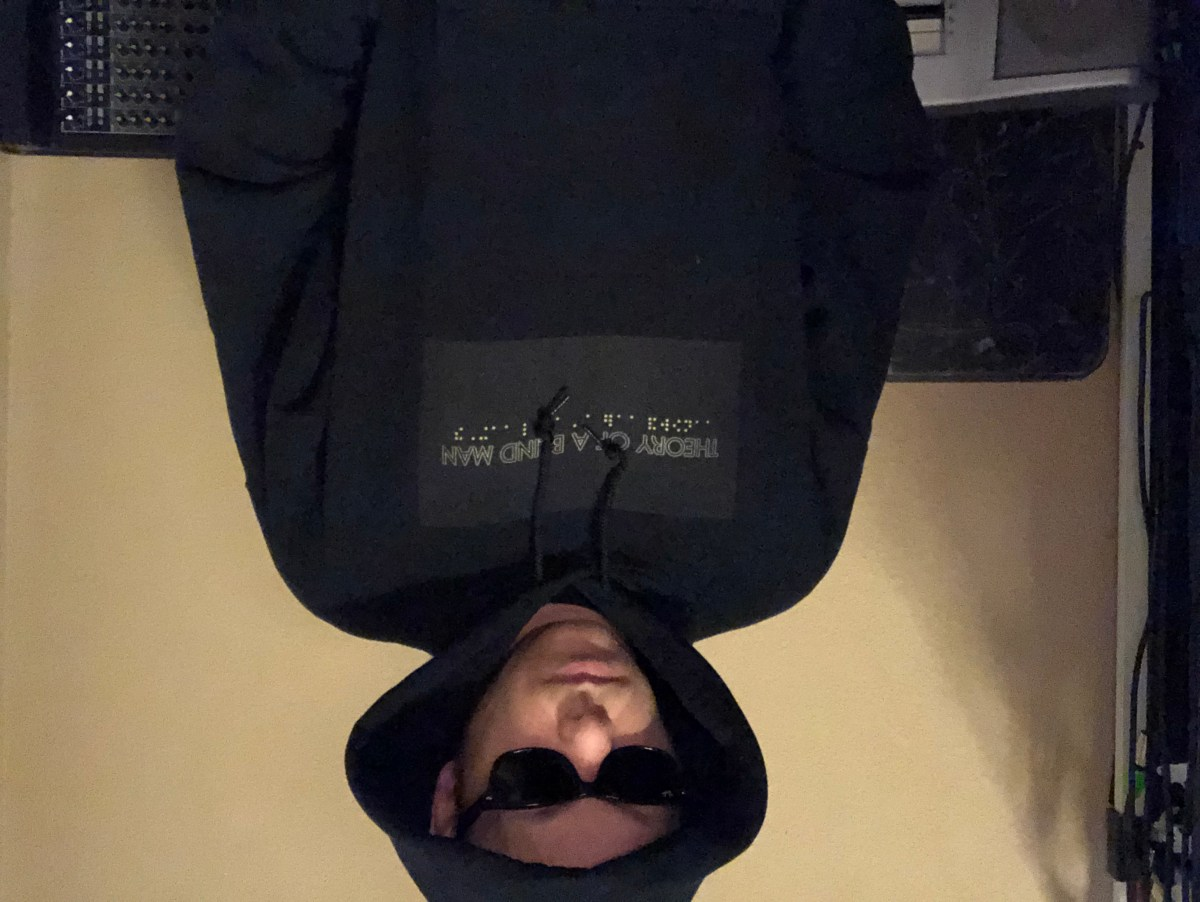 Whistler wearing a black hoodie with yellow star wars font that reads, theory of a blind man with braille below.