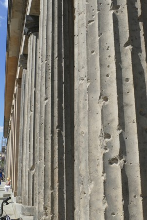 Columns still riddled with bullet holes, deliberately left as a memorial.