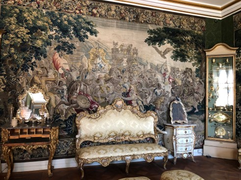 Rich tapestries line the walls.