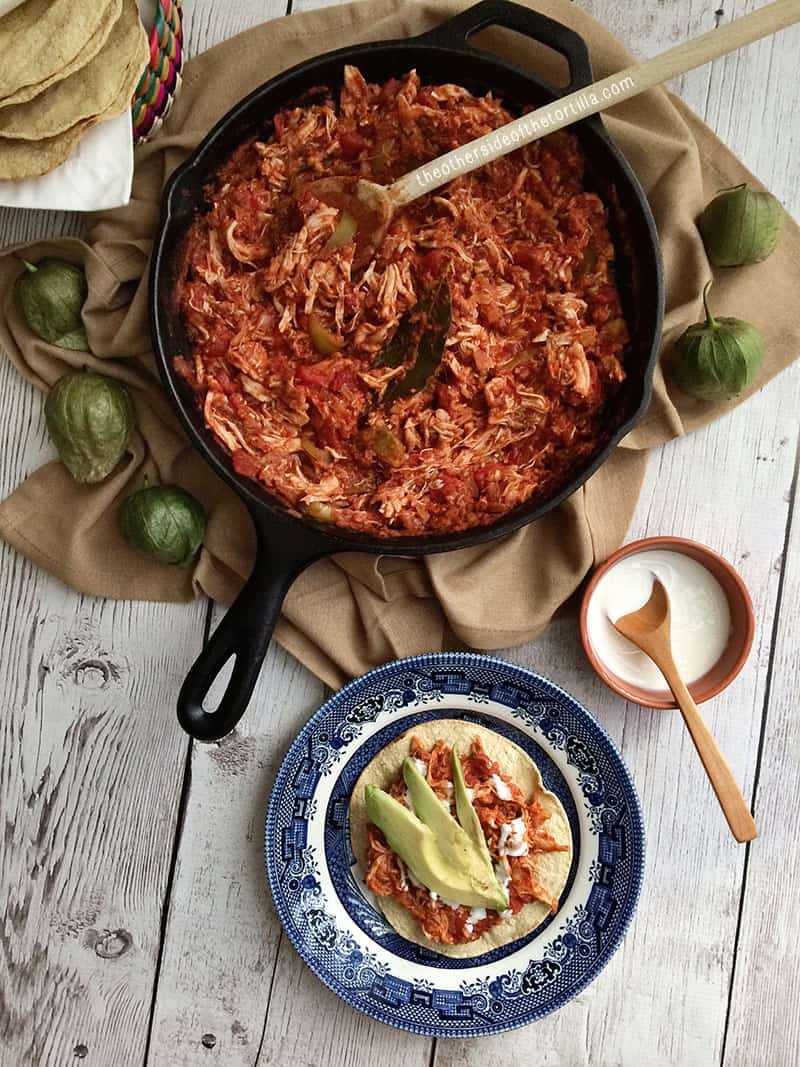 How to make tinga poblana, a Mexican dish with a tomato base and shredded chicken. Great for tostadas, tacos, served with rice, or as a quesadilla! This dish is also sometimes known as tinga de pollo or chicken tinga. Recipe via theothersideofthetortilla.com
