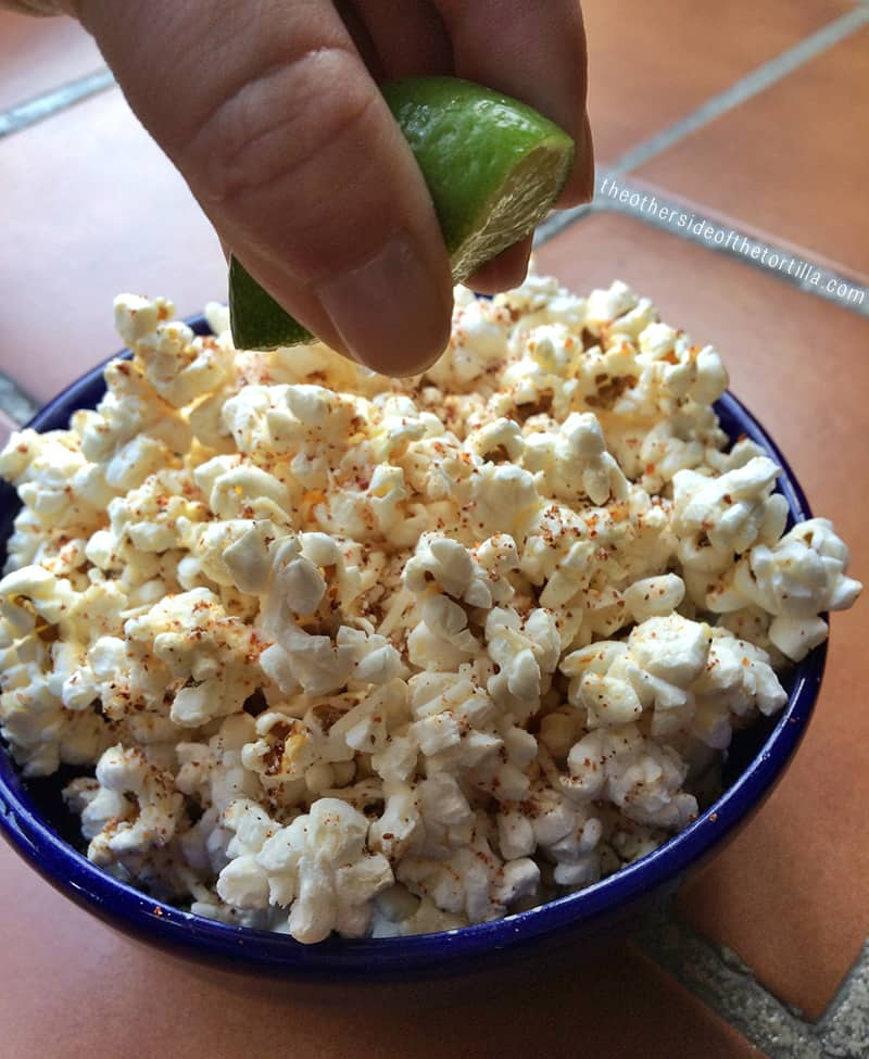 squeezing lime juice over popcorn