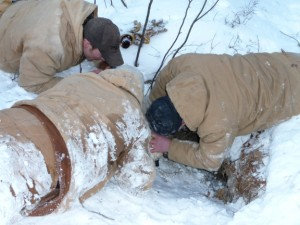 Bear researchers Karl Malcolm, Mike Gappa, and Dave McFarland maneuver a push-stick sedative syringe into a denned female and her yearling cubs.