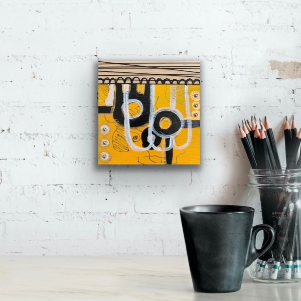 yellow and black wood block wall art above desk