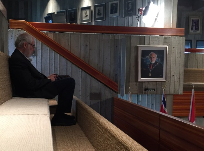 BREAKING NEWS: When former mayor Andy Wells watches a council meeting, he sits in the cheap seats directly under, and as close as physically possible to, his own mayoral portrait.
